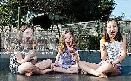 Girls eating popsicles on trampoline