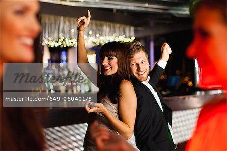 Smiling friends dancing in bar