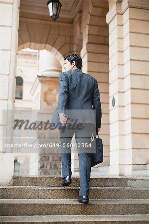 Businessman climbing steps of building