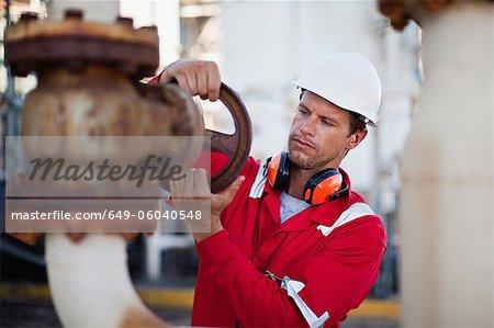 Worker adjusting gauge at chemical plant