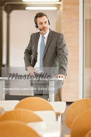 Businessman wearing headset at podium