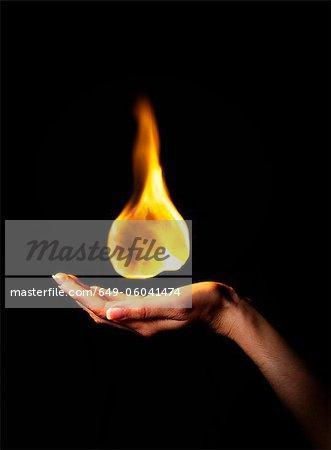 Hand holding burning flame