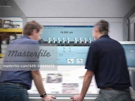 Printers examining printing press