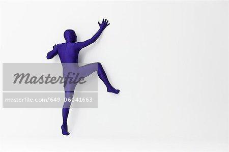 Man in bodysuit scaling wall