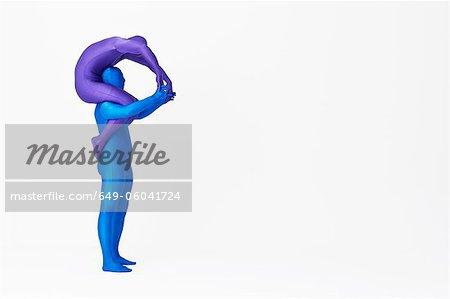 Men in bodysuits making the letter P