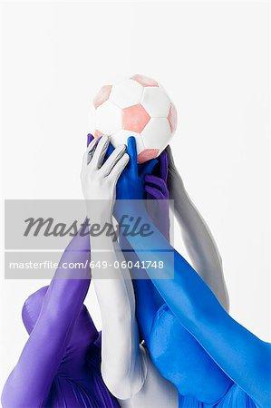 Men in bodysuits holding soccer ball