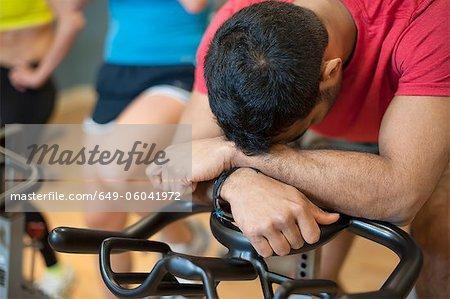 Man resting on spin machine in gym