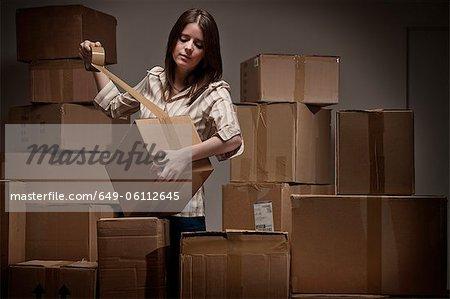 Teenage girl taping up cardboard boxes