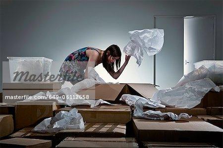 Teenage girl unpacking cardboard boxes