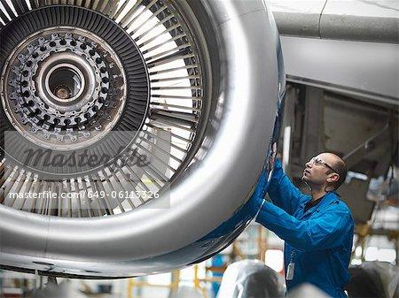Worker examining airplane engine