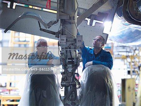 Worker adjusting airplane machinery