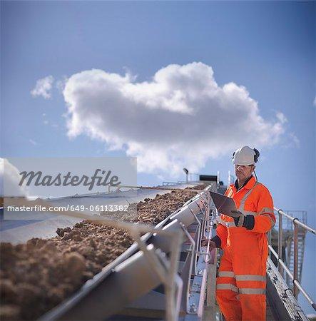 Worker with clipboard by conveyor belt