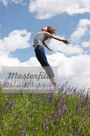 Woman jumping over tall grass