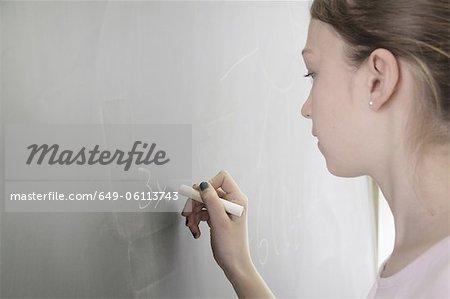 Student writing math on chalkboard