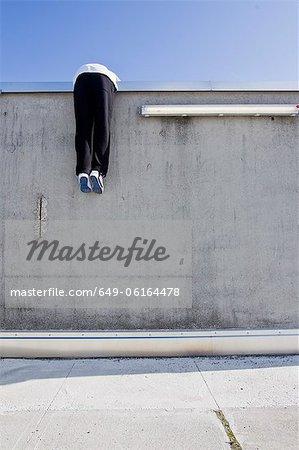 Man scaling wall on city street
