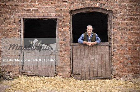 Farmer standing at gate of barn