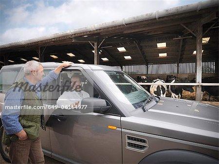 Farmer talking to veterinarian in car
