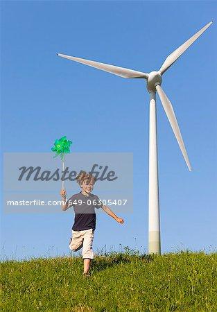 Boy with pinwheel by wind turbine