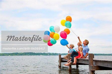 Family holding balloons on wooden pier