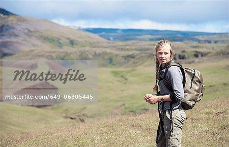 Hiker wearing backpack on hillside