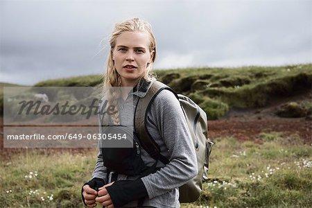 Hiker carrying backpack on hillside