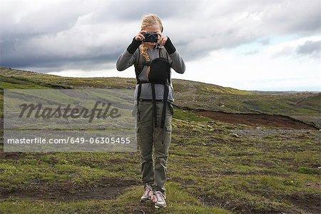 Hiker taking pictures on hillside