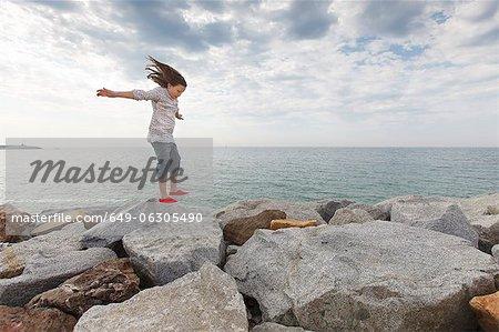 Girl playing on rocks at beach