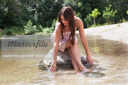Teenage girl sitting on rock in stream