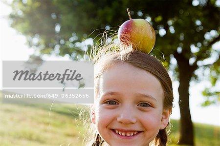 Smiling girl balancing apple on head