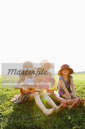 Smiling girls relaxing in grass