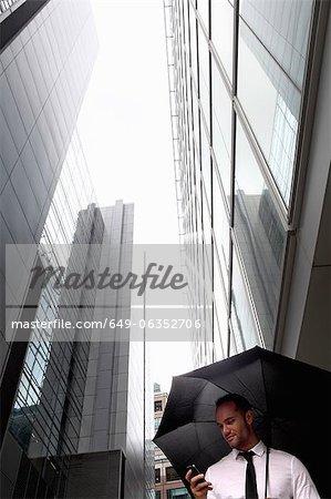 Businessman walking under umbrella