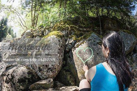 Woman drawing heart on rocks