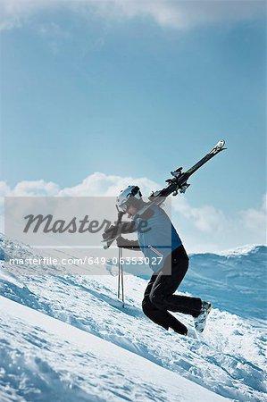 Skier climbing up snowy mountainside