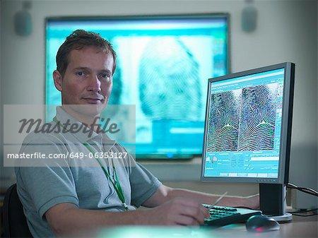 Forensic scientist at computer desk