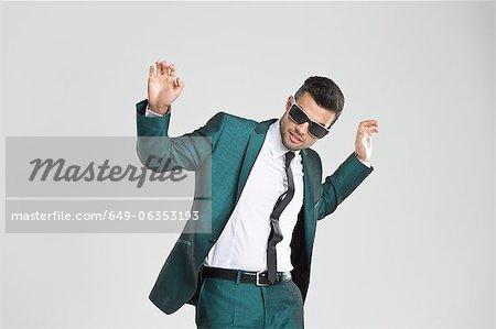 Businessman in sunglasses dancing