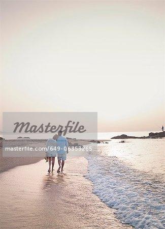 Older couple walking in waves on beach