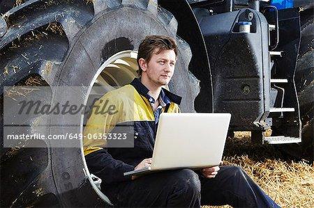 Farmer using laptop in field