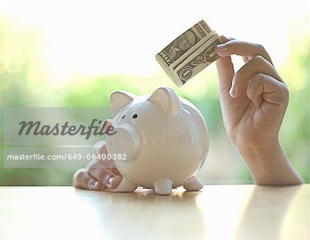 Hang putting dollar bill in piggy bank