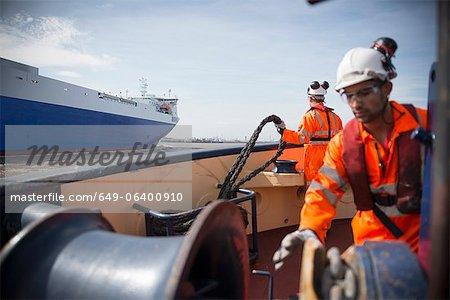 Workers on tug boat reeling in rope