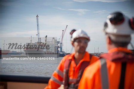 Container ship sailing into urban harbor