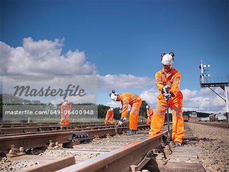 Railway workers adjusting train tracks