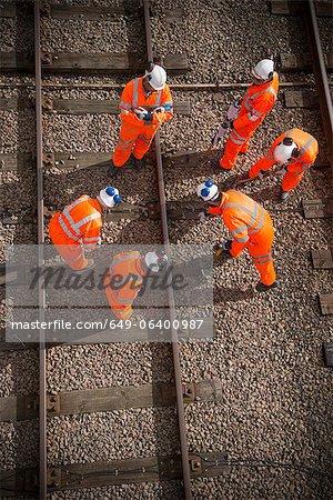 Railway workers examining train tracks