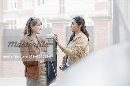 Women charging electric car on street