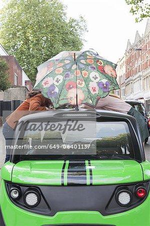Couple balancing umbrella on car roof