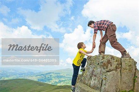 Boys climbing rural rock formation