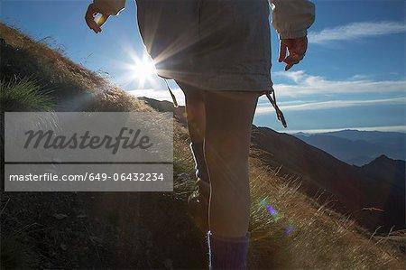 Woman hiking on rural hillside
