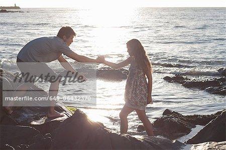 Couple climbing rocks on beach