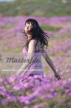 Woman walking in field of flowers