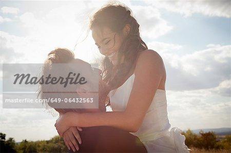 Newlywed groom holding bride outdoors