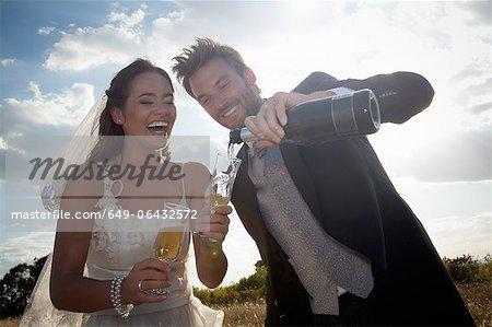 Newlywed couple having champagne